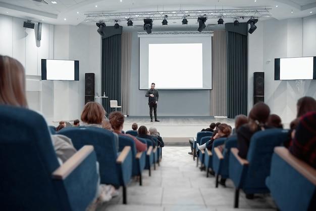 Orateur debout près du grand écran lors d'un séminaire d'entreprise