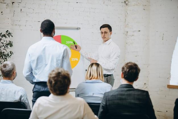 Orateur masculin donnant une présentation dans le hall à l'atelier universitaire. salle d'audience ou de conférence