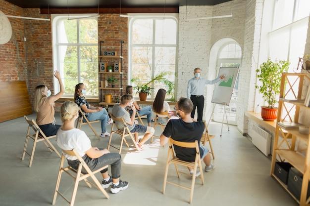 Orateur masculin faisant une présentation dans le hall de l'atelier universitaire audience ou salle de conférence