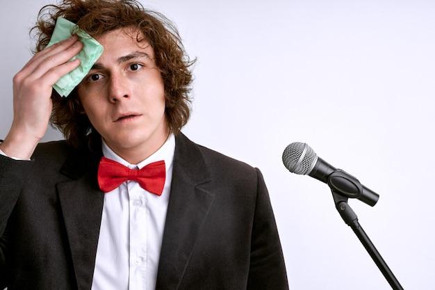 Orateur public caucasien nerveux et timide avec microphone, l'étudiant a peur de prononcer un discours devant une foule de personnes ou un public. visage en sueur, homme tenant un micro. mauvaise présentation