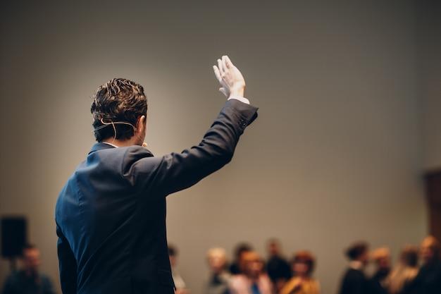 Orateur sur scène lors d'une conférence d'affaires.