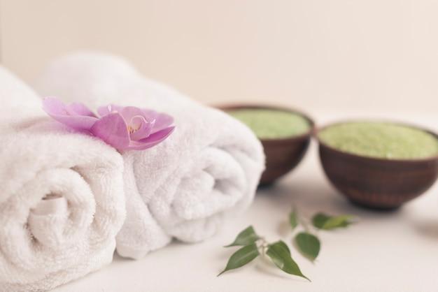 Orchidée sur une serviette roulée avec du sel de spa sur fond blanc