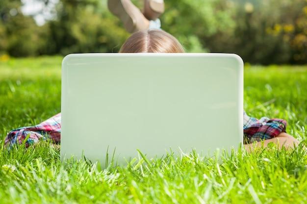Ordinateur et air frais. femme se cachant le visage derrière un écran d'ordinateur portable en position couchée sur l'herbe dans le parc