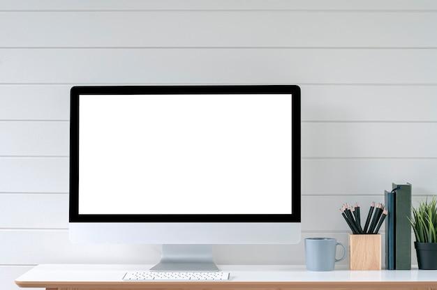 Ordinateur de bureau à écran blanc dans une salle de bureau minimale avec décorations et espace de copie.