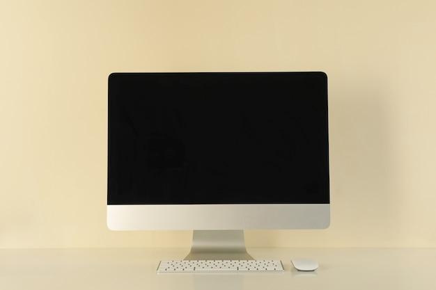 Ordinateur de bureau à écran blanc sur fond beige