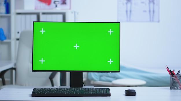 Ordinateur de bureau avec écran vert à l'hôpital et médecin spécialiste en arrière-plan. bureau avec écran remplaçable utilisé par un spécialiste de la médecine à l'hôpital et en uniforme.