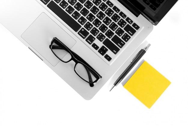 Ordinateur de bureau isolé avec lunettes, stylo et bloc-notes sur fond blanc