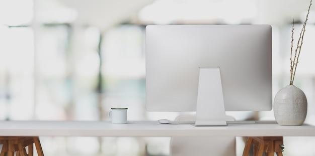 Ordinateur de bureau sur une table blanche et une tasse de café dans un bureau moderne