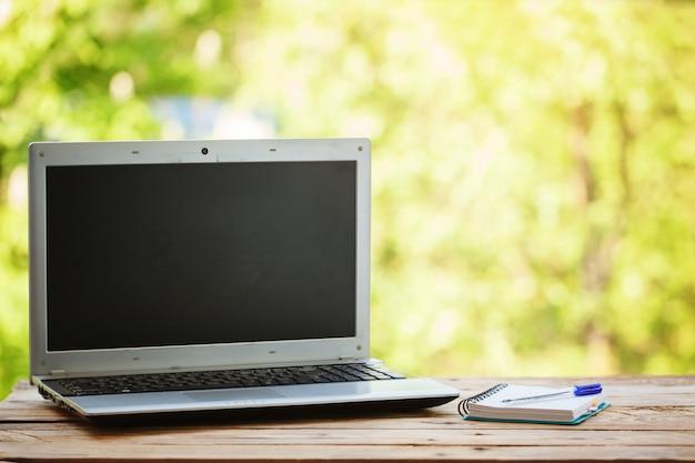 Ordinateur avec cahier sur table en bois et fond de nature
