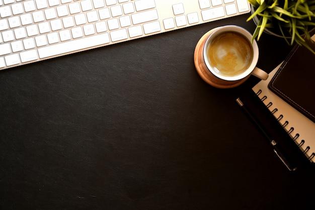 Ordinateur de clavier de bureau en cuir foncé moderne, lunettes, tasse à café, plante d'intérieur et espace de copie