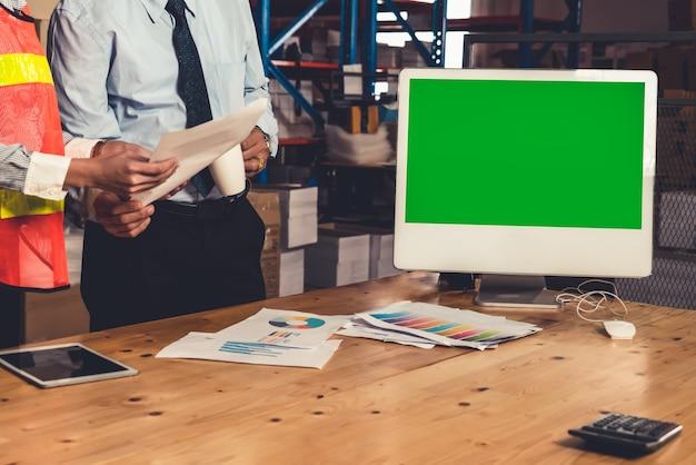 Ordinateur avec écran vert dans l'entrepôt