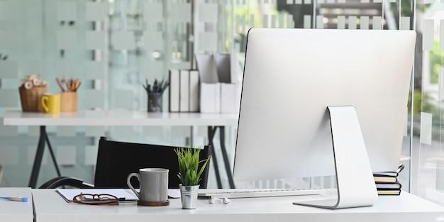 Ordinateur de l'espace de travail mettant sur un bureau de travail blanc entouré de tasse de café, plante en pot, document, pile de livres, clavier et souris sans fil sur bureau moderne