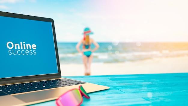 L'ordinateur est posé sur une table avec vue sur la mer. et une fille est debout détendue.