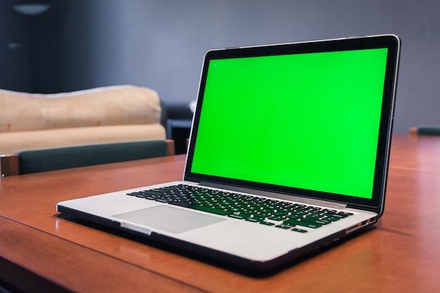 Ordinateur isolé avec écran vert dans un salon.