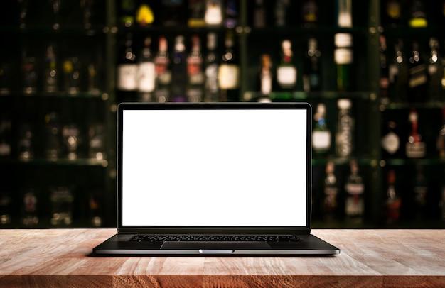 Ordinateur moderne, ordinateur portable sur comptoir bar avec fond de bouteille de vin flou