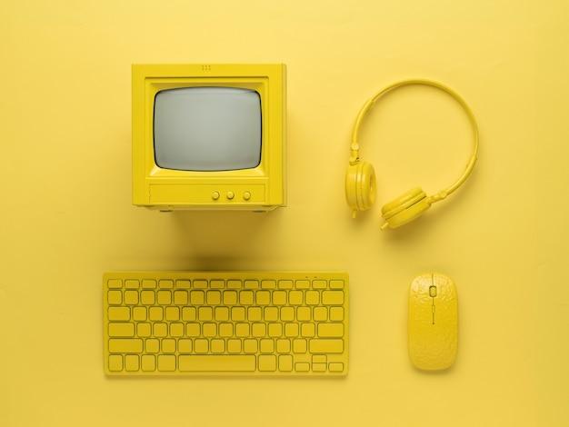 Ordinateur personnel avec accessoires de style jaune sur fond jaune. mise à plat.