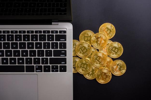 Ordinateur et pièces d'or avec symbole bitcoin sur fond noir.