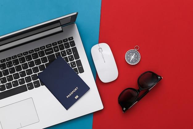 Ordinateur portable et accessoires de voyage sur rouge-bleu. concept de voyage de planification