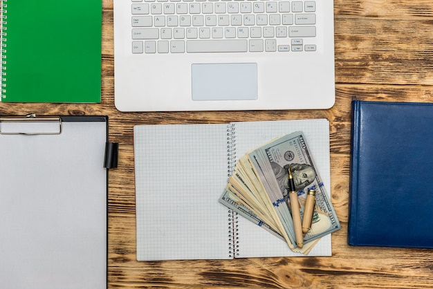 Ordinateur portable, agenda et billets en dollars