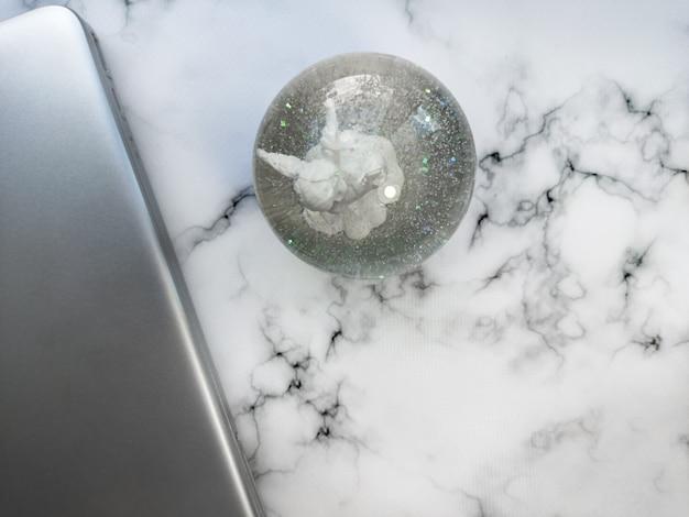 Ordinateur portable d'arrière-plan de travail à domicile propre et globe de neige sur une table en marbre blanc