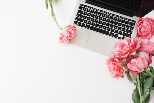 Ordinateur portable et belles fleurs de tulipes pivoine rose sur blanc