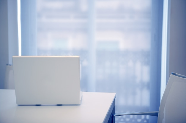 Ordinateur portable blanc ouvert sur une pièce blanche, lumière bleue venant de la fenêtre