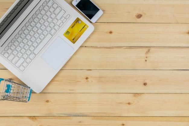 L'ordinateur portable blanc avec téléphone intelligent, carte de crédit et le modèle de caddie sur le fond de la table en bois. achats en ligne.