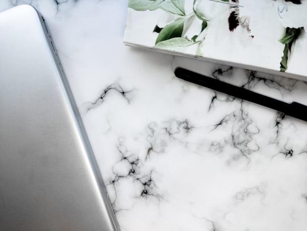 Ordinateur portable et bloc-notes d'arrière-plan de travail à domicile propre sur une table en marbre blanc