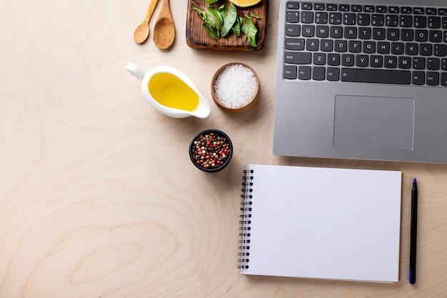 Ordinateur portable, bloc-notes et épices sur une table en bois avec espace de copie. concept de cours de cuisine en ligne.