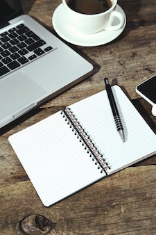 Ordinateur portable, bloc-notes et stylo sur la table avec une tasse de café