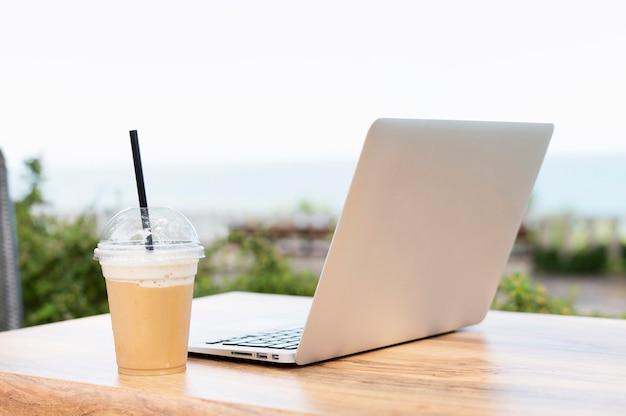 Ordinateur portable et boisson sur table à l'extérieur