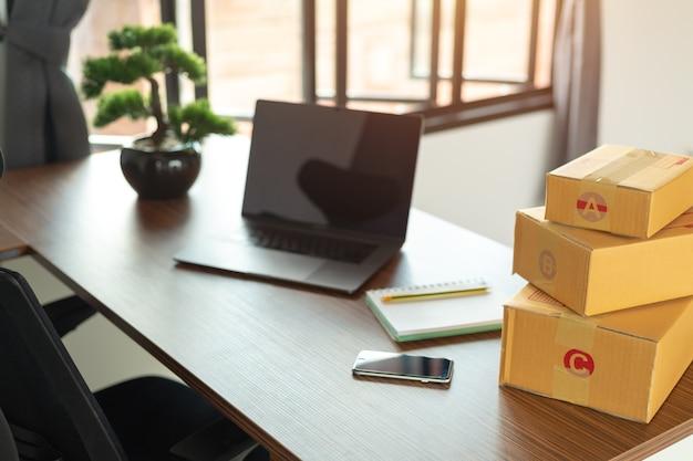Ordinateur portable, boîte de carton, colis de marchandises à livrer aux clients.