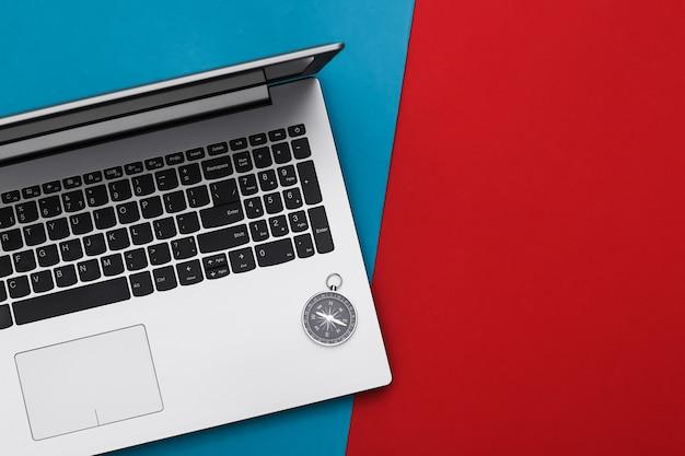 Ordinateur portable et boussole sur rouge-bleu. concept de voyage ou d'entreprise en ligne