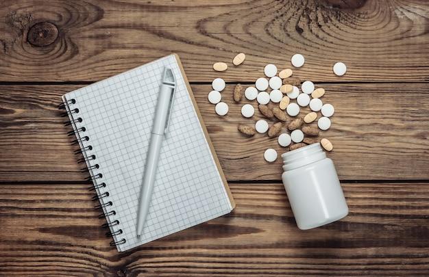 Ordinateur portable et bouteille de pilules sur une table en bois
