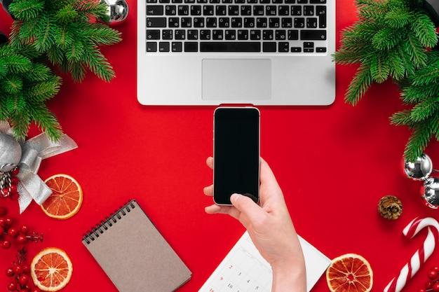 Ordinateur portable avec des branches d'arbres de fourrure et des décorations de noël sur le rouge