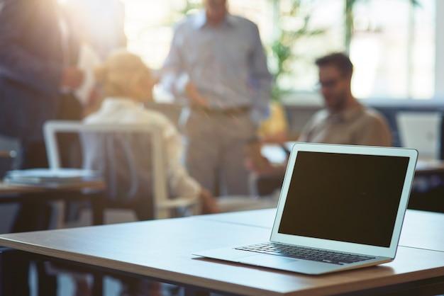 Ordinateur portable sur un bureau en bois dans le bureau moderne avec un groupe d'hommes d'affaires en arrière-plan