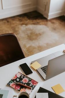 Ordinateur portable sur un bureau avec un cahier fleuri
