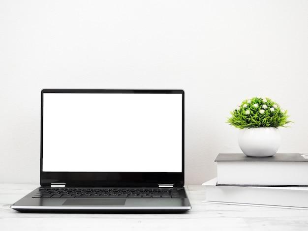 Ordinateur portable sur le bureau avec espace de travail livre et vase à la maison