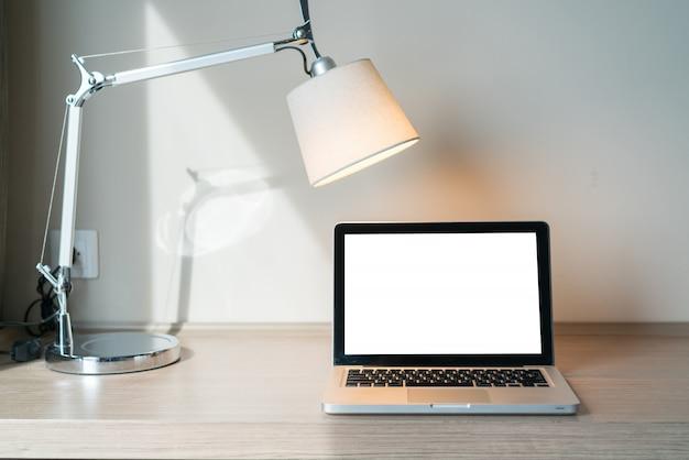 Ordinateur portable sur un bureau avec lampe
