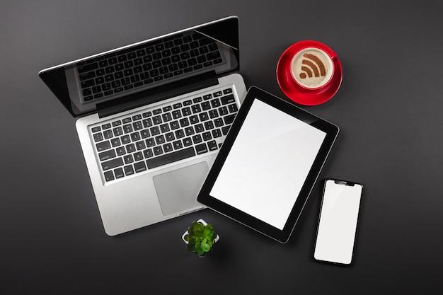 Ordinateur portable sur un bureau noir avec une tasse de café, un téléphone et un signe wifi fonctionnent dans les réseaux sociaux t