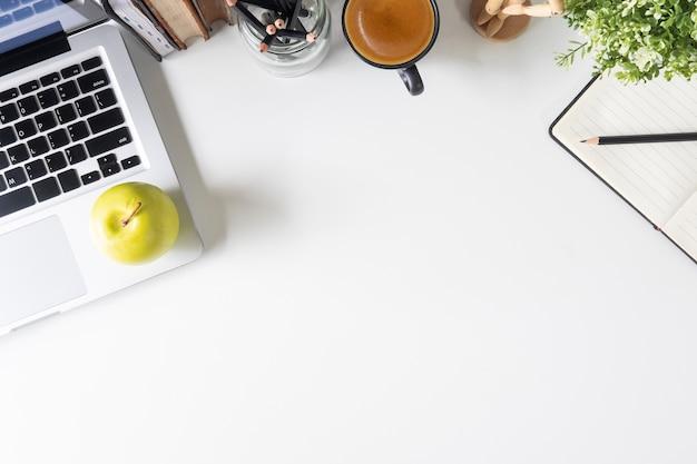 Ordinateur portable de bureau, papier pour ordinateur portable, crayon, livre et café sur l'espace de travail de tableau blanc.