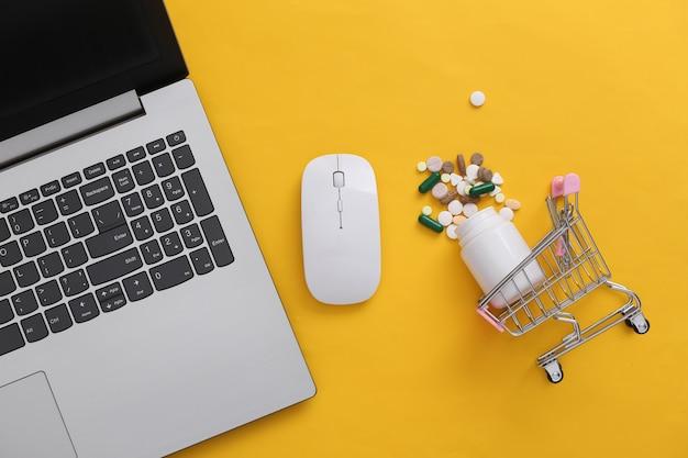 Ordinateur portable et caddie avec bouteille de pilules sur fond jaune. shopping en ligne. vue de dessus. mise à plat