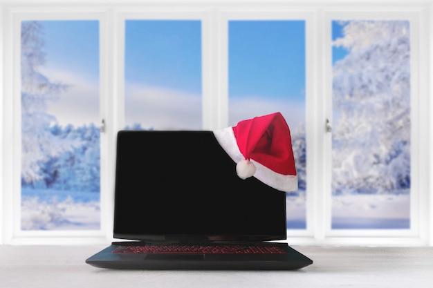 Ordinateur portable et cadeaux sur la table avec un chapeau de père noël à la maison avec une vue panoramique à travers