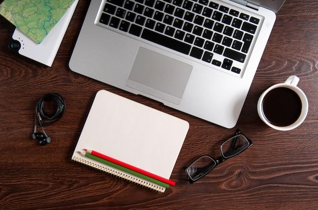 Ordinateur portable avec café chaud et carte sur table en bois