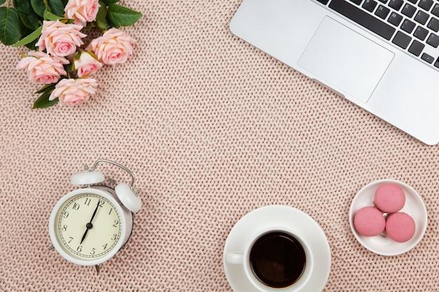 Ordinateur portable, café, gâteaux, roses, horloge sur couverture tricotée