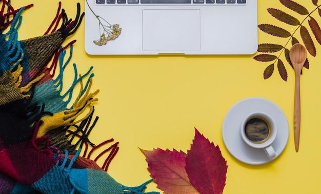 Ordinateur portable avec café, herbier et couverture sur fond jaune. l'automne.