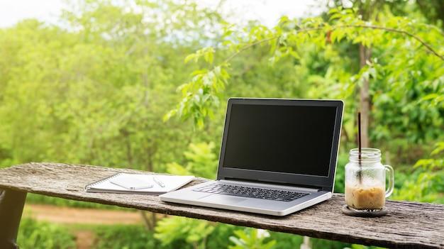 Ordinateur portable et café latte glacé sur une table en bois.