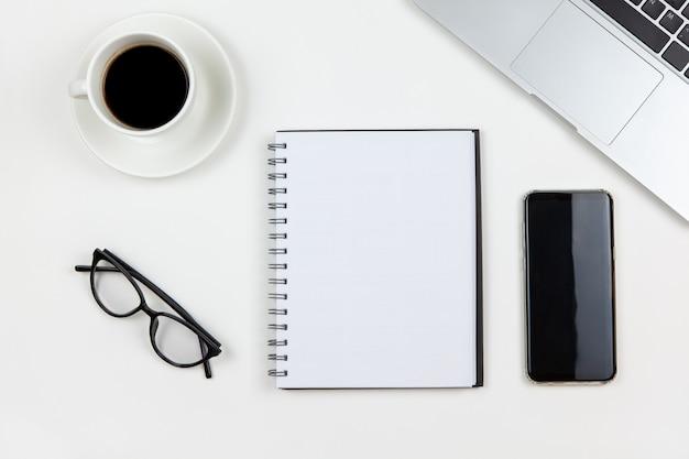 Ordinateur portable, café, ordinateur portable, smartphone, lunettes sur fond blanc