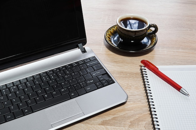 Ordinateur portable, cahier papier avec stylo et tasse de café sur la table en gros plan