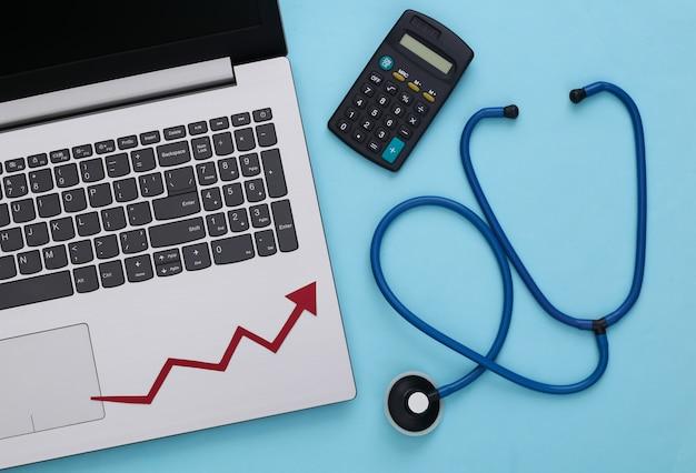 Ordinateur portable, calculatrice, stéthoscope avec une flèche de croissance sur un bleu. hausse des prix des médicaments.